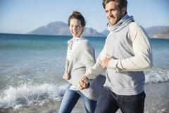 Stock Photo of Young couple holding hands and walking on beach