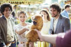 Cheerful woman reaching for soft toy in amusement arcade Stock Photos