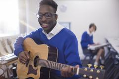 Portrait of smiling male student playing acoustic guitar in classroom Stock Photos