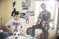 Two teenage boys playing music in room - stock photo