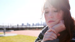 Beautiful Redhead sits in a park looking solemn Stock Footage