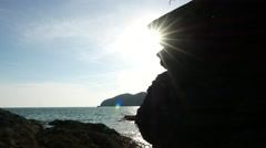 Man jump from rock to rock, high contrast stony cliff, back sun light Stock Footage