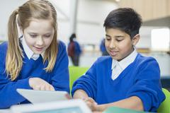 Boy and girl wearing school uniforms using digital tablet together Stock Photos