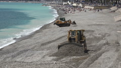 Municipal bulldozers maintain the stony beach, Nice, France Stock Footage