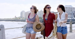 Three young women tourists on summer vacation walking on beach promenade Stock Footage