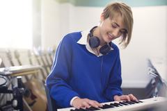 Smiling teenage student playing synthesizer Stock Photos