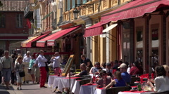 People sit at outdoor tables at restaurant in Cours Salaya old town, Nice - stock footage