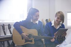 Female students playing acoustic guitar in classroom and using tablet pc Stock Photos