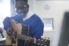 Young smiling student playing guitar in classroom - stock photo