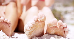 Close up of sandy feet wiggling toes three beautiful young woman sitting on - stock footage