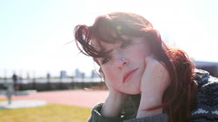 Beautiful Redhead sits in a park looking solemn - stock footage