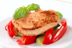 Pork cutlet with fresh red bell pepper and zucchini sticks - stock photo