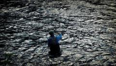 Angler Fishing Waist-Deep In River Stock Footage