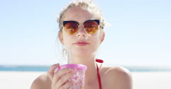 Close up portrait of beautiful young teenage girl drinking water from pink Stock Footage