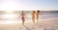 Young women running into ocean at sunset in slow motion playing in waves on Stock Footage