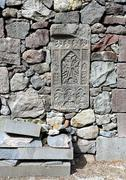 Old-time headstone built into a wall of gray stones - stock photo