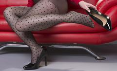 Woman sitting on a red sofa putting high heel shoes on Stock Photos