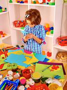Child painting at easel - stock photo