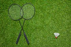 Crossed badminton rackets with white shuttlecock - stock photo