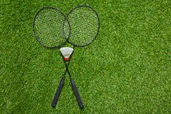 Badminton rackets with shuttlecock on the grass - stock photo