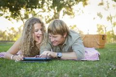 Playful Loving Couple Using a Touch Pad Computer at Their Picnic Outside. Stock Photos
