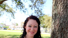 Stock Video Footage of Beautiful dark-haired woman smiles in a park