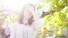 Beautiful dark-haired woman in a park under a tree - stock footage