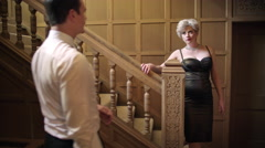 Attractive 1950s couple flirt at base of staircase 4K Stock Footage