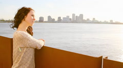 Beautiful dark-haired woman looks out over a bay - stock footage