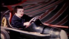 2198 - little boy on race car ride at amusement park - vintage film home movie Stock Footage