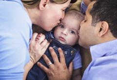 Mixed Race Parent Kissing Their Son Together. - stock photo