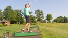 Slow motion front view of man hitting golf ball at driving range Stock Footage