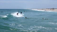 People surfing in Tavira Island beach, shot from jetty Stock Footage