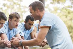 Team leader motivating tired teammates at boot camp Kuvituskuvat
