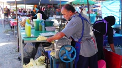 Man squeezes the juice from cane stalks on market in town of Kamala. Thailand Stock Footage