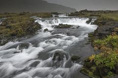 Waterfall through remote landscape, Vik, Iceland - stock photo