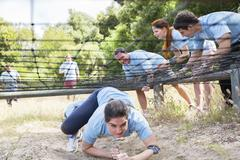 Determined woman crawling under net on boot camp obstacle course - stock photo