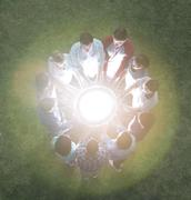 Team in circle surrounding glowing orb - stock photo