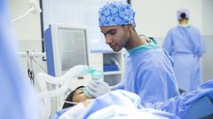 Anesthesiologist holding oxygen mask over patient's face in operating room Stock Photos