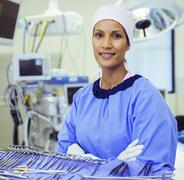 Portrait of confident surgeon near surgical scissors in operating room Stock Photos