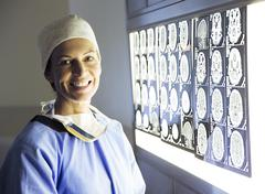 Stock Photo of Portrait of smiling surgeon reviewing MRI scans