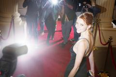 Portrait of smiling celebrity being photographed by paparazzi at red carpet Kuvituskuvat