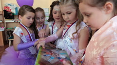 Kids look photoalbum with pictures. Nursery leaving party is in Russian daycare  Stock Footage