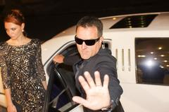 Bodyguard protecting celebrity from paparazzi outside limousine at event - stock photo