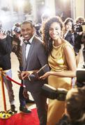 Smiling celebrity couple being photographed by paparazzi photographers at red Stock Photos