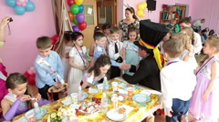 The Mad Hatter talks with children in nursery school during graduation day Stock Footage
