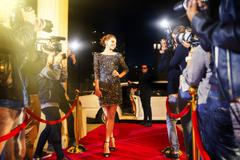 Celebrity arriving and posing for paparazzi photographers at red carpet event - stock photo