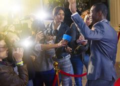 Celebrity waving at paparazzi photographers at red carpet event Kuvituskuvat