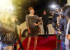 Celebrity arriving and posing for paparazzi photographers at red carpet event Stock Photos