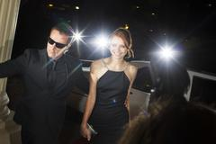 Bodyguard escorting smiling celebrity arriving at event Stock Photos